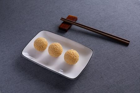 Fried hemp balls in white porcelain dishes with Red Wood Chopsticks