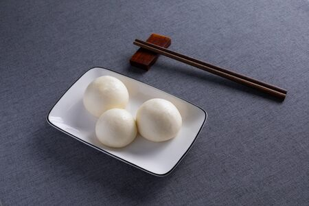 Chinese steamed bread arranged neatly in white porcelain dish.