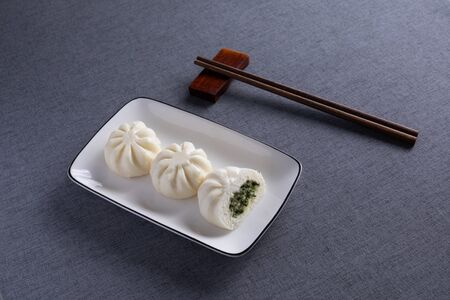 a dish of steamed buns with Red Wood Chopsticks