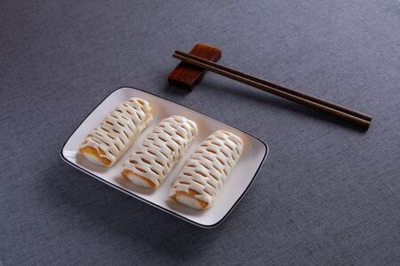 Bread rolls on white porcelain plates with red wood chopsticks