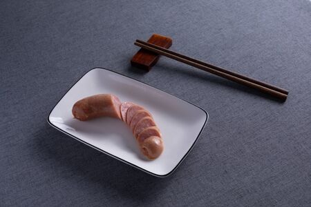 baked sausage on a white porcelain dish with Red Wood Chopsticks 스톡 콘텐츠