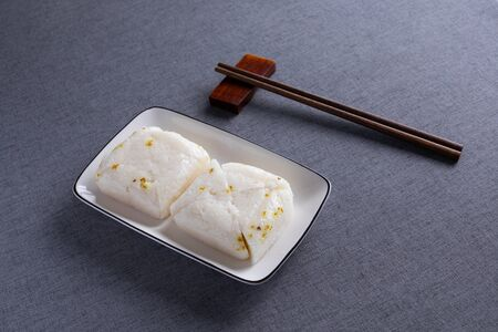 Osmanthus fragrans rice cake on white porcelain plate with red wood chopsticks Foto de archivo - 128746269
