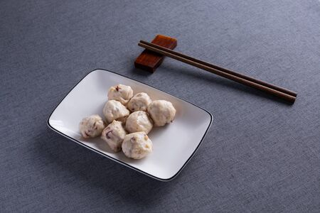 Pork balls on white porcelain plates with red wood chopsticks.