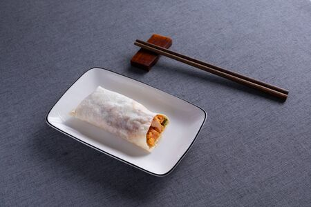 spring roll on a white plate with pepper jelly