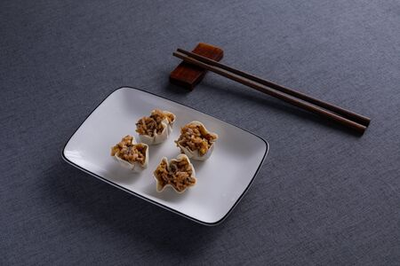 Shrimp and rice dumplings on white porcelain plates with red wood chopsticks