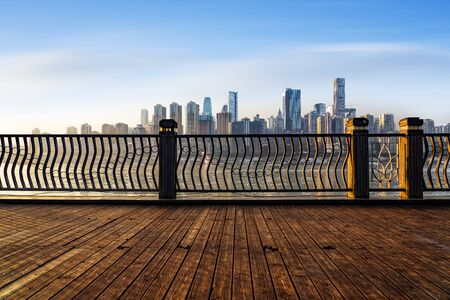 In front of the wooden platform the city skyline