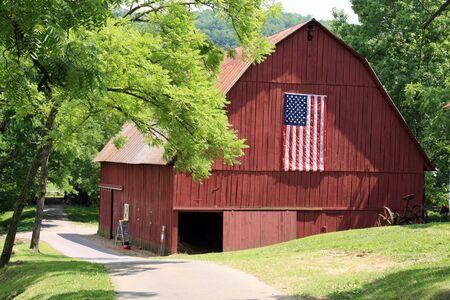 Aantrekkelijke nieuwe rode schuur met Amerikaanse vlag Stockfoto