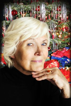 75s: Senior woman in front of a decorated christmas tree
