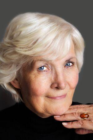 75s: Senior lady portrait on dark grey background