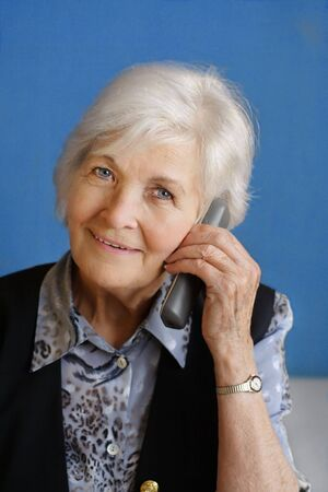 75s: Senior woman busy by telephone call