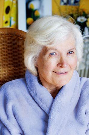 75s: Senior lady in bathrobe sitting in livingroom Stock Photo