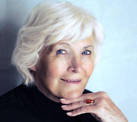 75s: Senior woman portrait on blue background