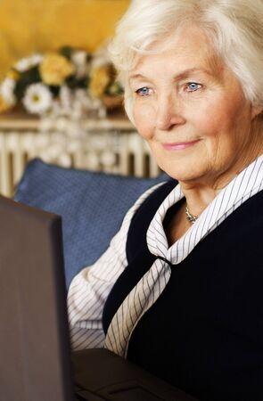 75s: Senior woman working on laptop Stock Photo