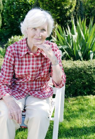 Senior woman sitting on a chair in the garden