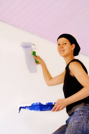 Woman painting a wall for renovation photo