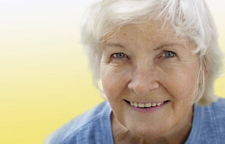 Natural senior woman portrait on yellow background Stock Photo