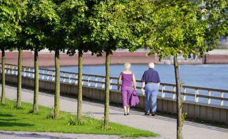 Senior couple at a sidewalk on a riverside Stock Photo