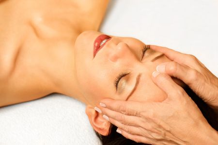 heal care: woman gets facial massage,closeup,on bright background Stock Photo
