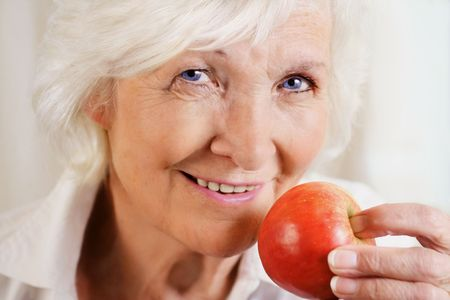 Happily senior woman holding red apple Stock Photo - 3725772
