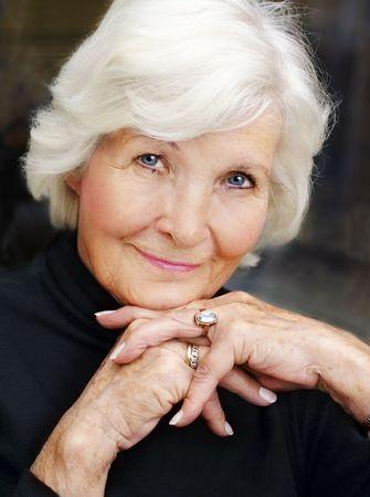 Senior woman portrait on dark background,crossed hands