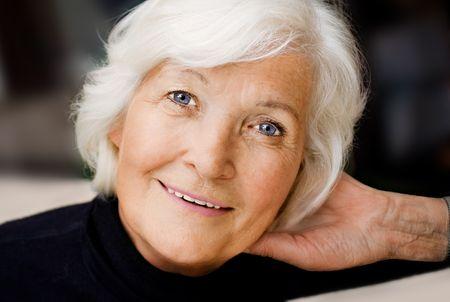 Senior lady portrait with hand on neck Stock Photo