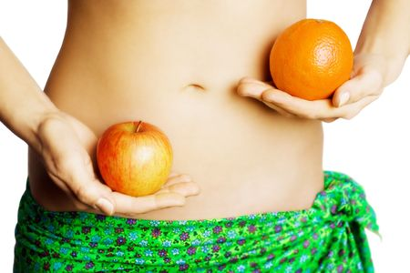 Hands holding apple and orange in front of womans belly
