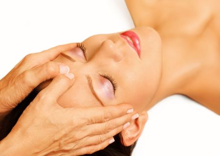 Young woman lying on her back, gets massage,reiki,acupressure on her head, focus on face and hands