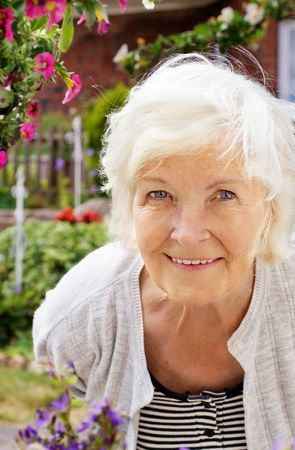 Senior woman portrait, outdoor, in front of the garden,smiling to camera Stock Photo