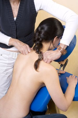 Young woman sitting on massage seat, getting massage treatment on her shoulder photo