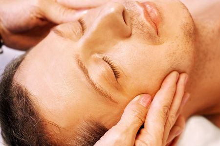 Mature man lying on his back, gets massage,reiki,acupressure on his face, focus on face and hands photo