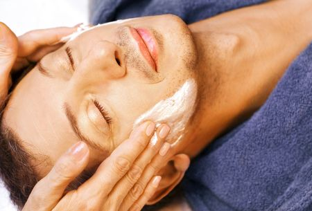 Middle-age man is getting cream mask and massage on his face Stock Photo