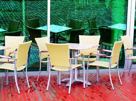 �mpty cafe on a rainy day in front of a green window with its  reflection, photo