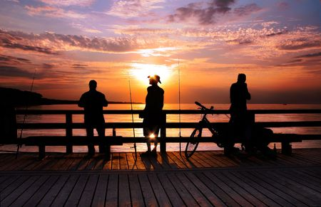 Three Angler standing on a bridge in the sunrise, backlite, Stock Photo