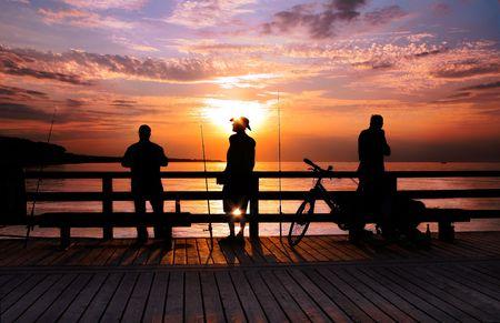 backlite: Three Angler standing on a bridge in the sunrise, backlite, Stock Photo