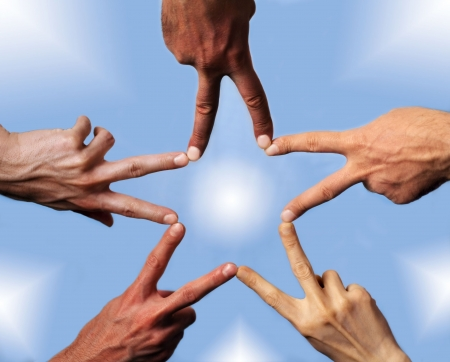 christmas ground: Five hands with different skin-color, their fingers building a star Stock Photo