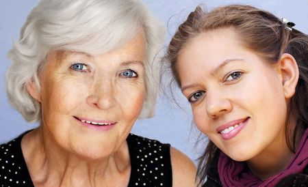 nearness: Grandmother and granddaughter looking at camera together,smiling Stock Photo