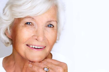 Beautiful senior woman laughing on white background photo