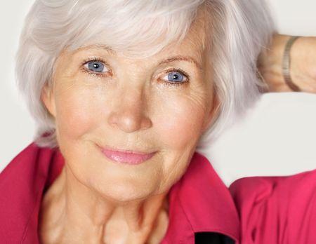 rides: Portrait de femme sup�rieurs avec des cheveux blanc et rouge blouse, tenue � gauche bras sur le c�t� et a la main dans les cheveux  Banque d'images
