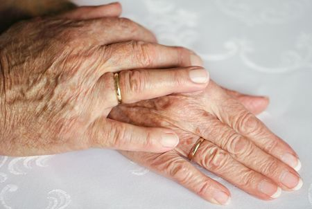 Two hands of an old couple, lying upon each other, with golden wedding rings Stock Photo