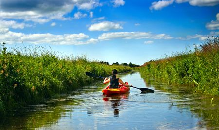 kayak: Girl with paddle and kayak on a small river in rural landscape