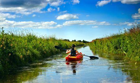 canoa: Joven de paddle y kayak sobre un pequeño río en paisaje rural