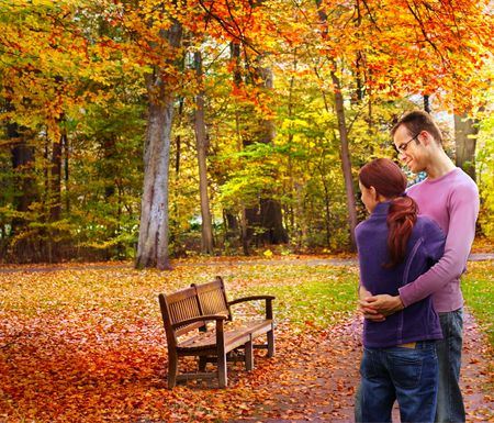Happy couple standing embraced in the autumnal park looking to a bench photo