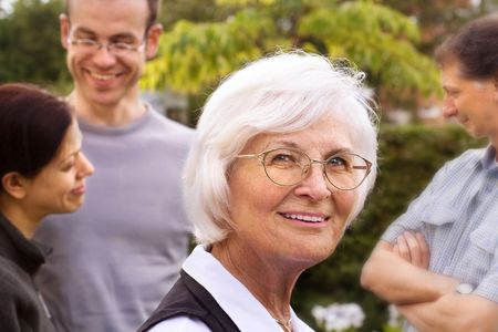 Senior woman smiling in front of three young people, outdoor Stock Photo