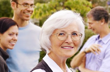 granddaughters: Senior woman smiling in front of three young people, outdoor Stock Photo