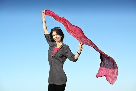 tunic: Senior woman with a blowing red scarf on a clear blue sky