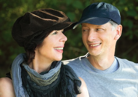 Middleage couple with scarf and cap smiling at each other, outdoors Stock Photo - 10836545