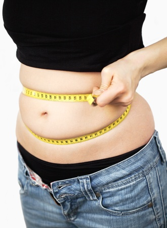 Woman with overweight is measering her waistline with a tape