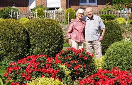 Senior couple in their garden with bushes and flowers photo