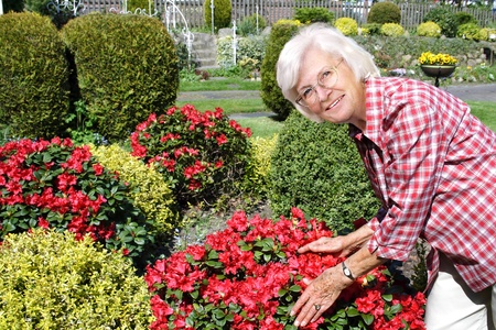 Senior woman in her garden with bushes and flowers