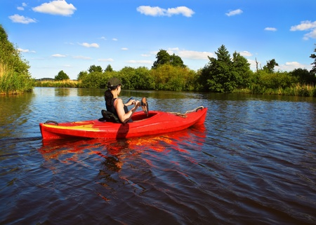 Girl with paddle and kayak on a small river in rural landscape Stock Photo - 12926457